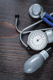 ヴィンテージの木製の背景医学概念に医学の聴診器と血圧モニター