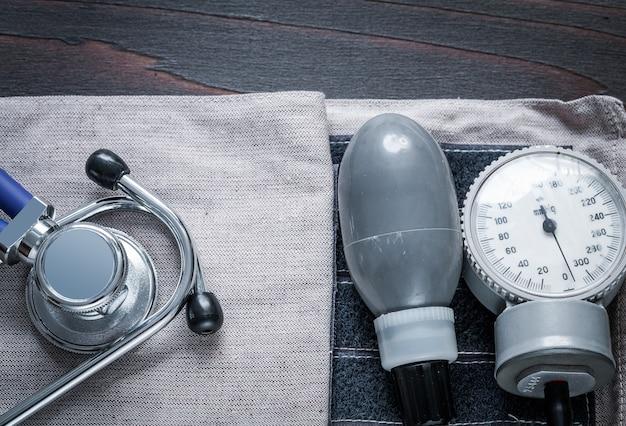 医学の聴診器とヴィンテージの木製の背景医学概念に圧力バンドと眼圧計