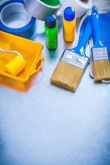 家庭用テープ保護手袋とメタリックな背景の建設コンセプトにペイントツールのセット