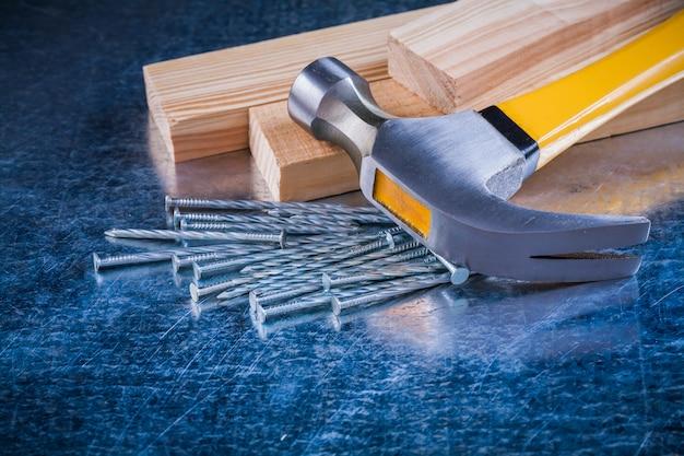 Металлический гвоздодер-гвоздодер и деревянные шпильки на поцарапанной металлической б