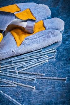 Защитные перчатки, гвозди и гвоздодер по поцарапанной метке