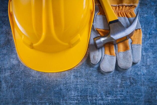 Защитные перчатки желтого строительного шлема и гвоздодер на царапине