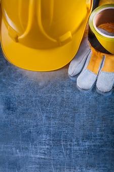 Защитная лента строительного шлема и защитные перчатки на поцарапанном м
