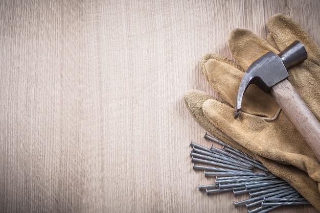Состав перчаток кожаные защитные перчатки и стальные длинные гвозди на деревянных фоне концепции строительства