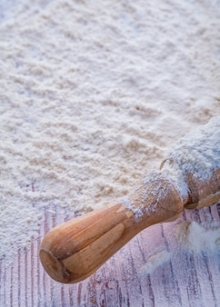 Скалка с мукой на деревянной доске еды и питья концепции