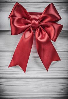 Рулон бумаги с красным бантом на деревянной доске