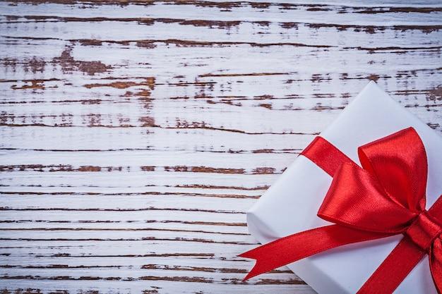 Подарочная коробка с красной лентой на старинной деревянной доске