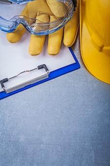 Защитные очки перчатки блокнот строительный шлем на металлическом столе