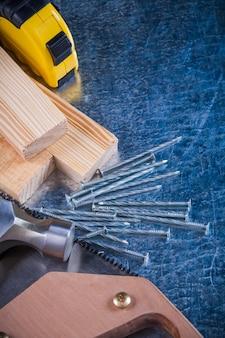 Набор металлических гвоздей молоток деревянные кирпичи ручная пила рулетка на поцарапанной металлической поверхности, концепция строительства