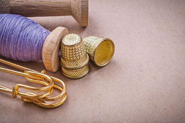 ミシン糸のスプールがヴィンテージのテーブルに安全ピンを指ぬき