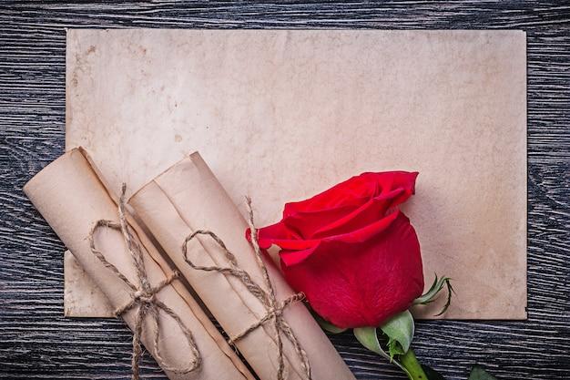 ヴィンテージ紙は木製のテーブルに赤い天然バラのつぼみをロールバックします