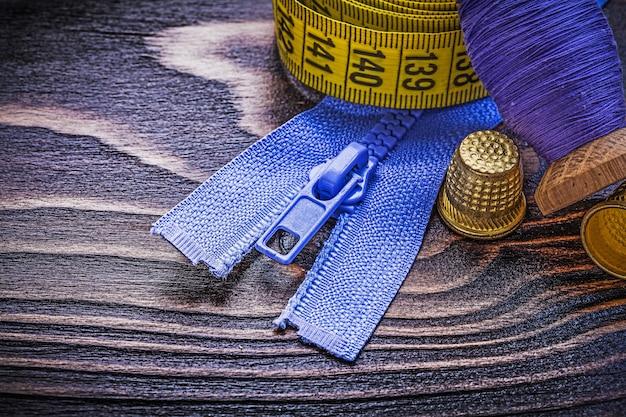 木の板の裁縫コンセプトに糸測定テープシンブルジッパーファスナーのビンテージスプール