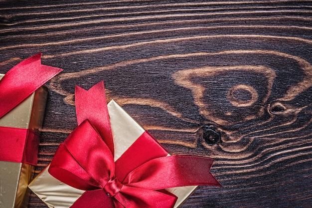 Коробки с красными присутствующими лентами на деревянной доске горизонтальная версия