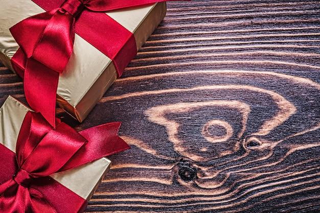 Завернутые подарочные коробки с красными атласными лентами на деревянной доске