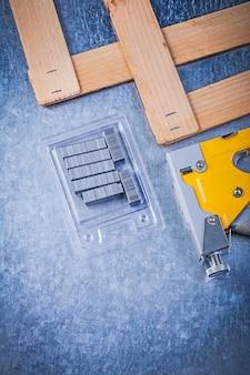 Ассортимент из сшивающего ружья металлический скрепляет деревянную доску на металлическом столе, концепция строительства
