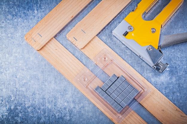 Коллекция степлером пистолет металлические скобы деревянные строительные доски на металлическом столе