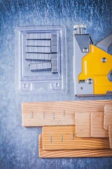 建設ホッチキスクロムの組成は、金属製のテーブルに木製の建築板をステープルします。