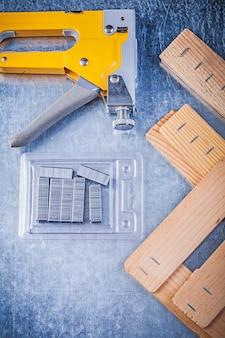 ストラップルガンクロムの組成は、金属製のテーブルに木製の建築板をステープルします。