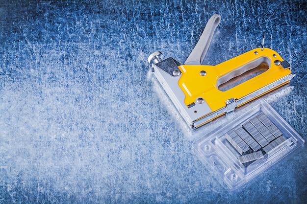 Строительные степлеры с хромированными скобами на поцарапанном металлическом столе