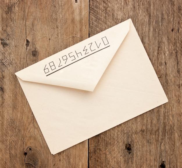 Старый почтовый конверт на деревянном фоне