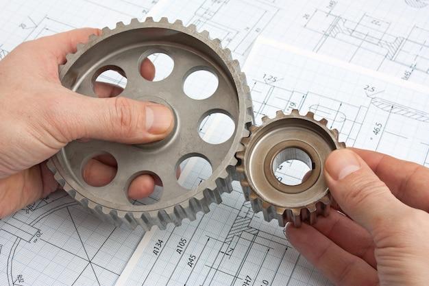 Технический чертеж и шестерни в руках