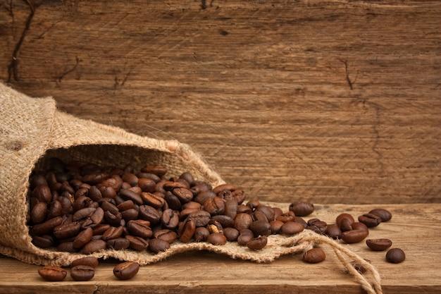 Кофейные зерна в сумке на деревянном фоне