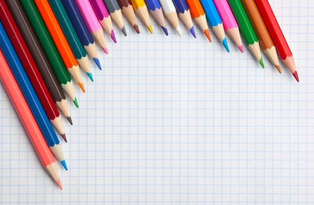 Цветные карандаши в школьной тетради