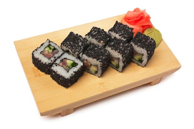 白で隔離される木製のプレートに伝統的なアジア料理の寿司