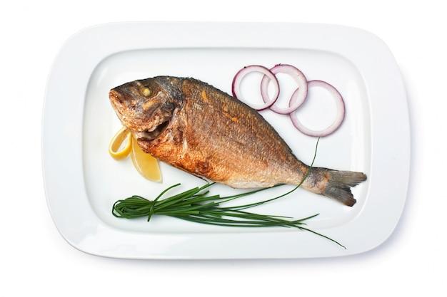 白で隔離される玉ねぎと揚げ魚の料理