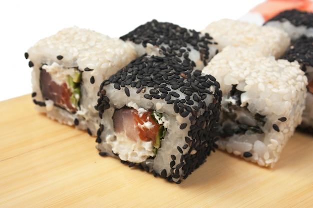 白い表面に分離された木製のプレートに伝統的なアジア料理の寿司
