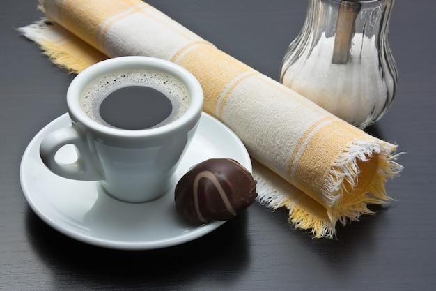 Чашка кофе и шоколадные конфеты на столе