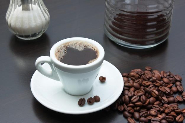 コーヒー豆と灰色のテーブルの上にカップの山