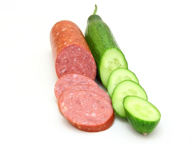 Свежая колбаса и огурец лежат рядом
