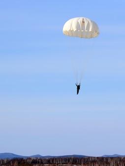 ジャンプ後のヘルメットの落下傘兵ジャンパー