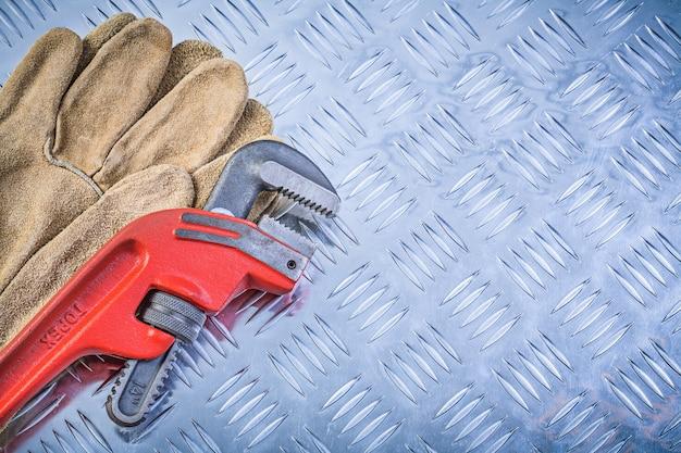 溝付き金属プレート上の安全手袋パイプレンチのペア