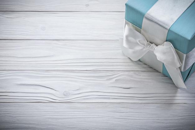 Синяя подарочная коробка с белой лентой на деревянной доске торжества концепции