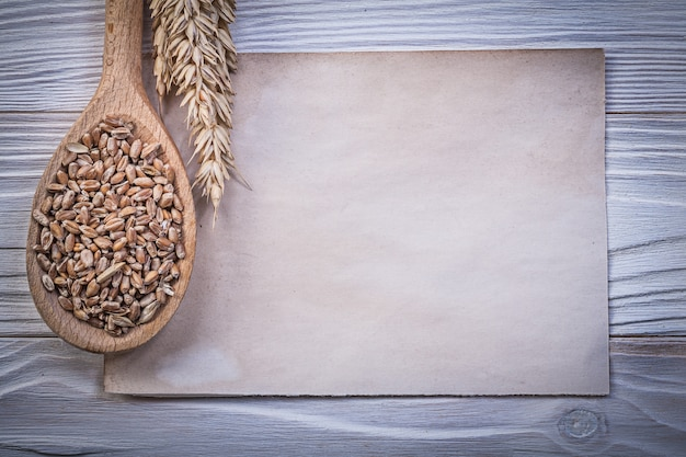 黄金の小麦ライ麦耳トウモロコシ木のスプーンヴィンテージ紙シートの木板の食べ物や飲み物のコンセプト