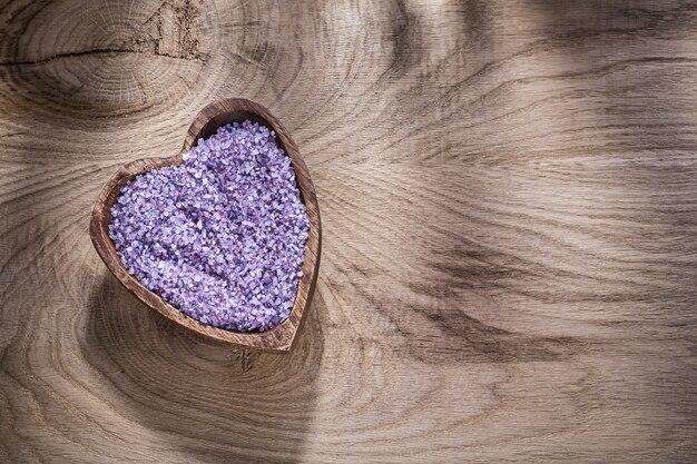 Чаша в форме сердца с морской солью лаванды на деревянной доске