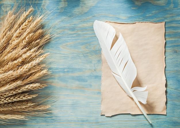 Рожь уши старинные лист бумаги перо на деревянной доске