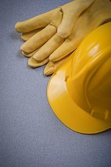 灰色の表面に黄色のヘルメットと革の保護手袋