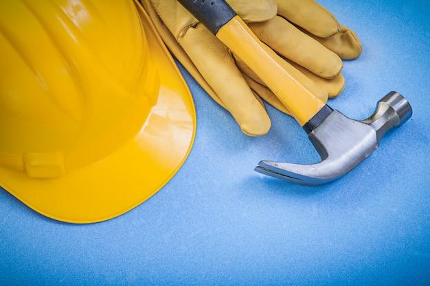 クローハンマー、革製保護手袋、青い表面に建物のヘルメット