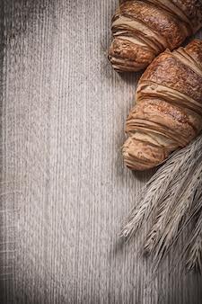黄金の小麦ライ麦の耳と木の板で焼きたてのクロワッサン