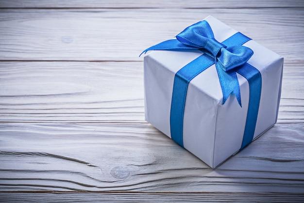 木の板に青いリボン付きプレゼントボックス