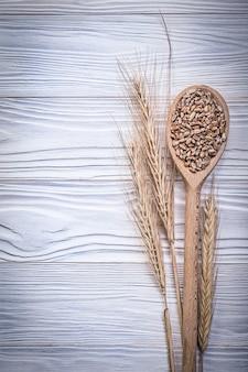小麦ライ麦の穂と木の板に種子と木のスプーン
