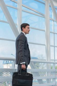 空港またはオフィスビルの都市環境で歩いているビジネスマン