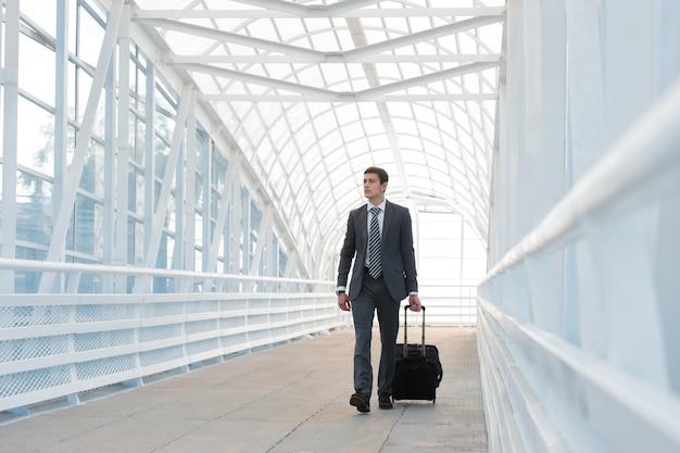 空港の都市環境で歩いているビジネスマン