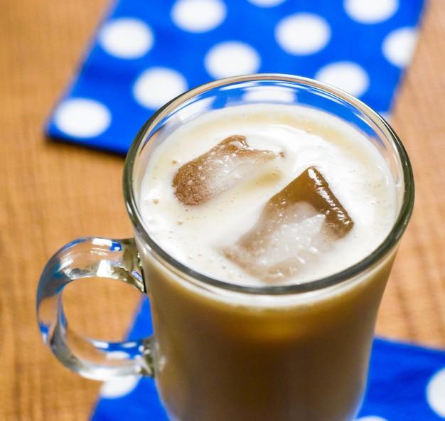 木製のテーブルの上のガラスのマグカップでアイスコーヒー