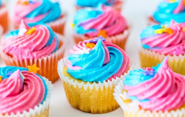パーティーのお祝いのためのパステル調の虹色のフロスティングとユニコーンカップケーキ