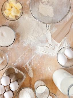 Фон рамки выпечки ингредиенты. плоские плоские белые заготовки готовятся к приготовлению на деревянной разделочной доске.