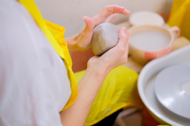 女性の手が陶芸の粘土をこねる